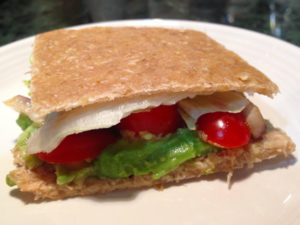 Avocado, mushroom, onion, lettuce and grape tomato sandwich